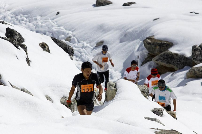 In this photograph received by Himex, the organisers of the Tenzing-Hillary Everest Marathon on May 29, 2014, marathon participant Sudip Kulung (left) takes part in the event near Gorapshep at Mount Everest Base camp in Nepal. -- PHOTO: AFP/HIMEX