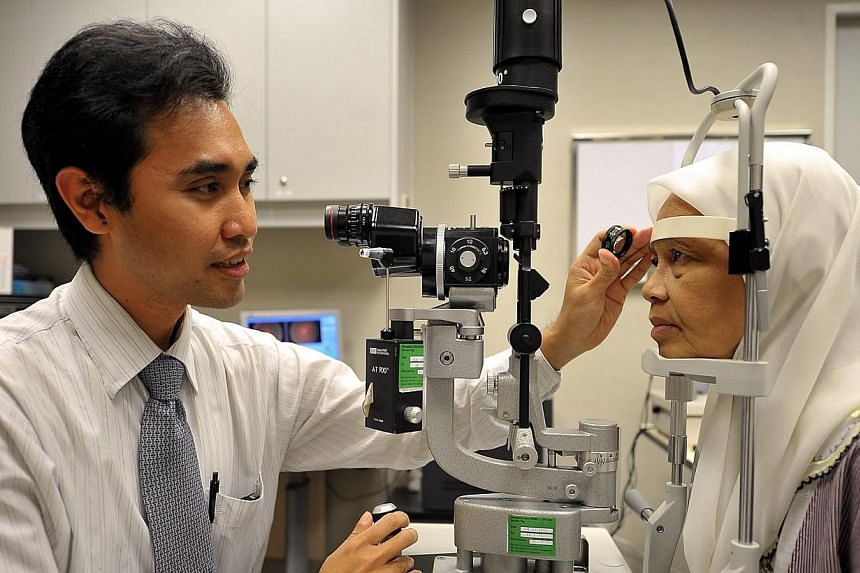 "Dr Ainur Rahman Anuar, a clinical research fellow at the Singapore Eye Research Institute (Seri), checking the eyes of a patient using a ""slit lamp"" at the Singapore National Eye Centre (SNEC) on Feb 17, 2012. The Singapore National Eye Centre ("