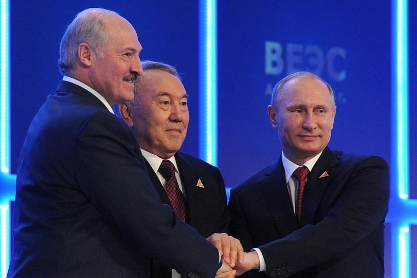 (From right) Russian President Vladimir Putin shakes hands with his Kazakh counterpart Nursultan Nazarbayev and Belarussian counterpart Alexander Lukashenko during a regular meeting of the Supreme Eurasian Economic Council in Astana on May 29, 2014.