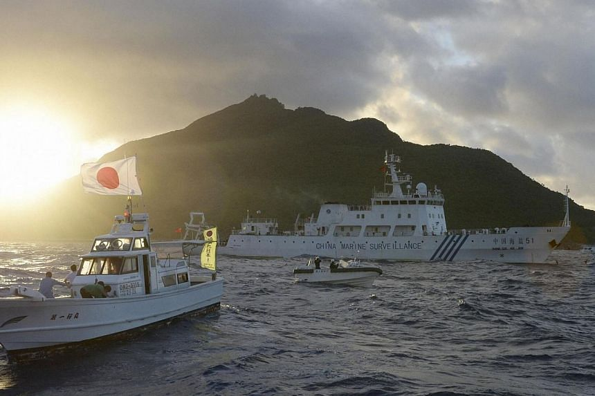Chinese marine surveillance ship Haijian No. 51 (centre) sails near Japan Coast Guard vessels (right and left) and a Japanese fishing boat (front 2nd left) as Uotsuri island, one of the disputed islands, called Senkaku in Japan and Diaoyu in China, i