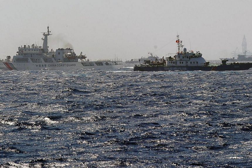 This picture taken from a Vietnam Coast Guard ship on May 14, 2014 shows a Vietnam Coast Guard ship (2nd right, dark blue) trying to make way amongst several China Coast Guard ships near to the site of a Chinese drilling oil rig (right, background) b