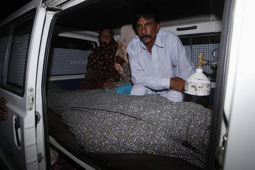 Mohammad Iqbal sits next to his wife Farzana's body, who was killed by family members, in an ambulance outside of a morgue in Lahore on May 27, 2014. -- PHOTO: REUTERS