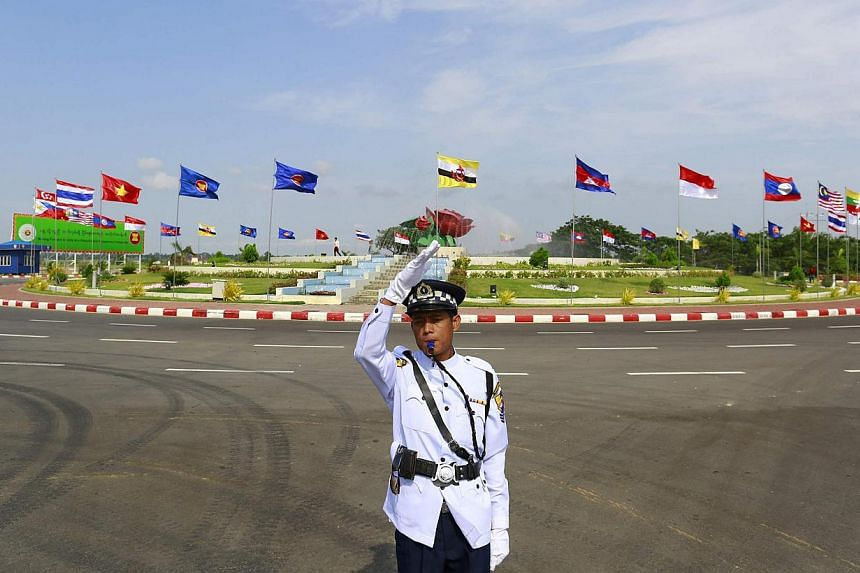A traffic policeman standing before country flags at the 24th Asean summit in Naypyidaw on May 10. The year 2015 will mark a major turning point in the region's history. South-east Asians need to re-learn the lesson of the earlier generation of natio