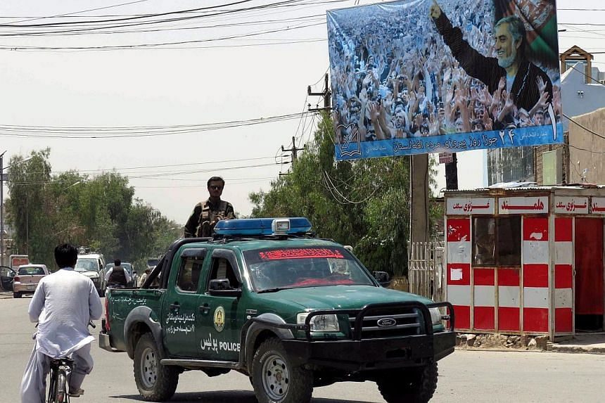 An Afghan police vehicle passes by electoral billboards of presidential candidate Abdullah Abdulah in Kandahar, Afghanistan, 29 May 2014. -- PHOTO: EPA