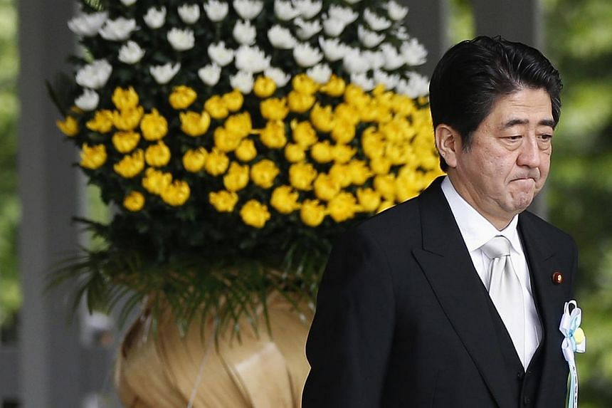 Japan's Prime Minister Shinzo Abe walks after offering a flower for Japan's unidentified war dead, during a ceremony at Chidorigafuchi National Cemetery in Tokyo May 26, 2014. --PHOTO: REUTERS