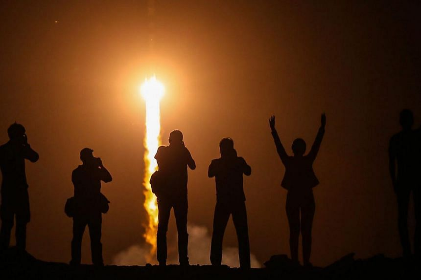 Spectators watch as the Soyuz TMA-13M rocket is launched with Expedition 40 Soyuz Commander Maxim Suraev, of the Russian Federal Space Agency, Roscosmos, Flight Engineer Alexander Gerst, of the European Space Agency, ESA, and Flight Engineer Reid Wis