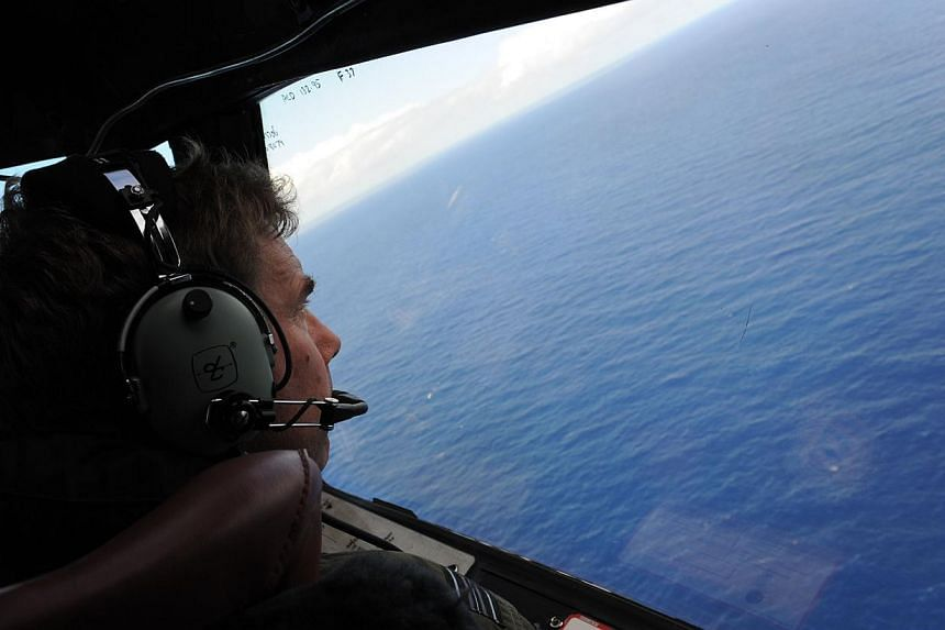 Royal New Zealand Airforce P-3K2-Orion aircraft co-pilot Brett McKenzie helps to look for objects during the search for missing Malaysia Airlines flight MH370, off Perth on April 13, 2014. -- PHOTO: AFP