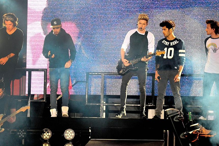 British Group One Direction perform in concert in Santiago, on April 30, 2014. Louis Tomlinson of British pop phenomenon One Direction has apparently filmed himself smoking what he called a joint, sharing it with bandmate Zayn Malik, in footage circu