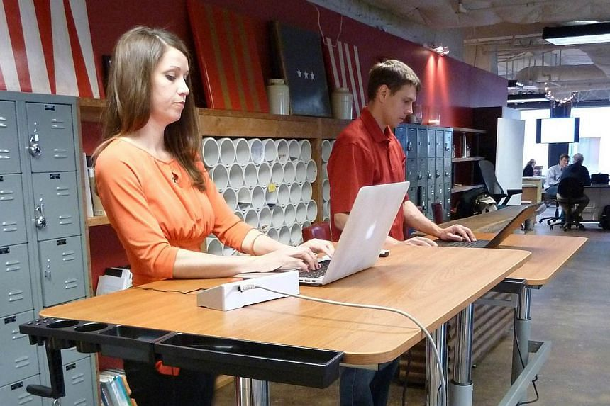 Kathleen Hale (L), 34, co-founder and CEO of the company Rebel Desk, which sells standing desks and treadmills desks, shows how to use the treadmill and standing desk in Washingon, DC, on May 7, 2014. -- PHOTO: AFP
