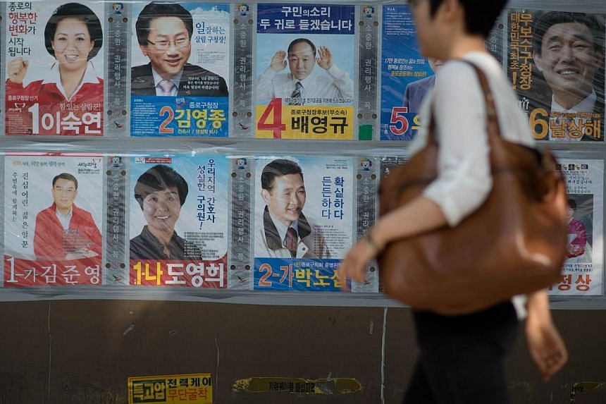 The posters of local election candidates are dispolayed on a wall in Seoul on May 29, 2014. -- PHOTO: AFP