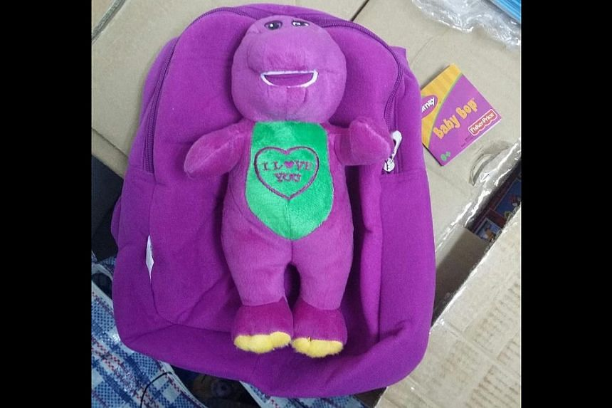 Singapore Customs enforcement officers found 159 cartons and nine sacks containing an assortment of toys, water bottles, bags and accessories featuring popular superhero and comic characters such as Barney (above) in the container. -- PHOTO: SIN