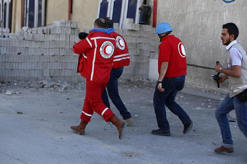 Red Crescent staff run for cover after Syria's air force hit the town of Douma, northeast of Damascus, where they were distributing aid parcels along with a UN team on May 24, 2014. -- PHOTO:AFP