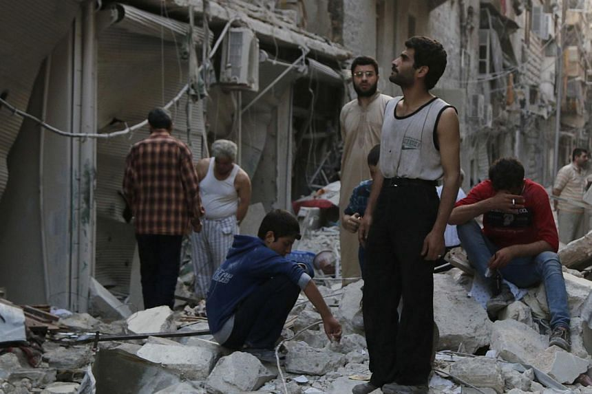 People react among debris of damaged buildings along a street at a site hit by what activists said was a barrel bomb dropped by forces loyal to Syria's President Bashar al-Assad in Aleppo's Bustan al-Qasr neighborhood on May 28, 2014. -- PHOTO: REUTE