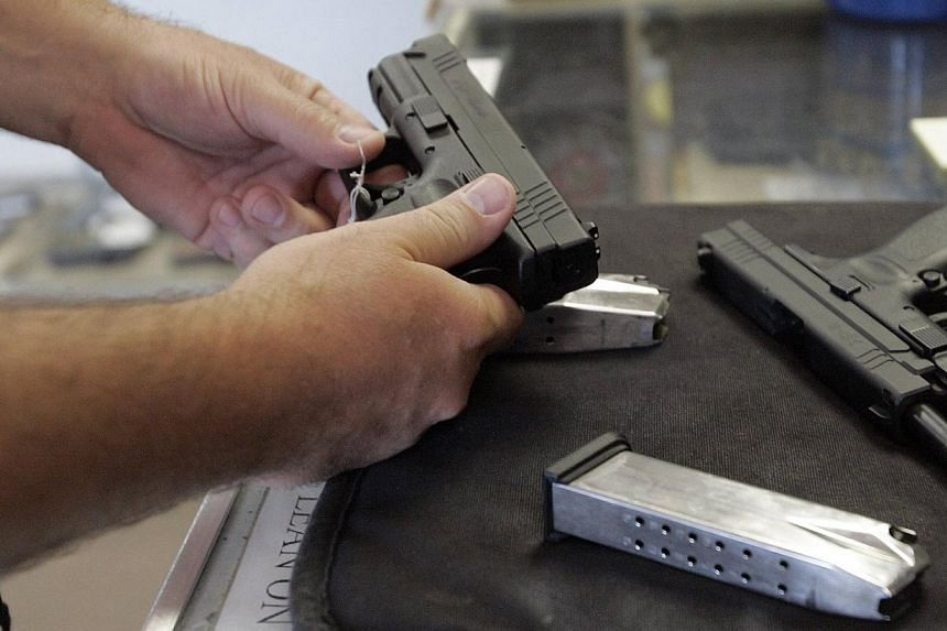 A customer inspects a 9mm handgun at Rink's Gun and Sport in the Chicago, suburb of Lockport, Illinois on June 26, 2008. -- PHOTO: REUTERS