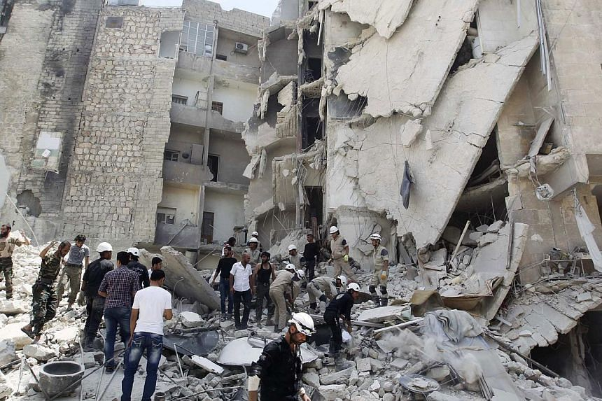 Civil Defence members, rebel fighters and civilians search for survivors at a site hit by what activists said was a barrel bomb dropped by forces loyal to Syria's President Bashar al-Assad in al-Qarlaq neighbourhood of Aleppo on May 29, 2014. -- PHOT