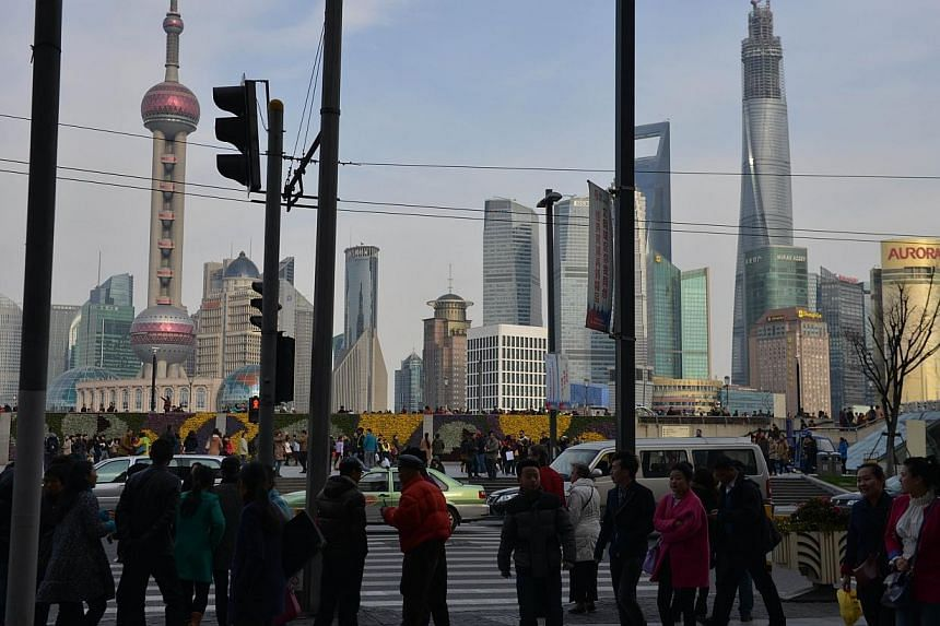 Pedestrians cross the street in Shanghai's financial district on the Bund on March 13, 2014. Business leaders were told that China remains an important part of maintaining Singapore's economic progress at a ceremony Friday evening. -- PHOTO: AFP