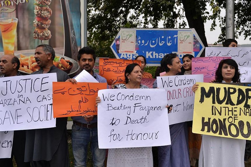 Pakistani human rights activists hold placards as they chant slogans during a protest in Islamabad on May 29, 2014 against the killing of pregnant woman Farzana Parveen was beaten to death with bricks by members of her own family for marrying a man o