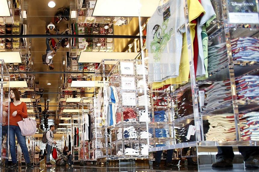 A woman looks at t-shirts in a clothing retail store at Ginza shopping district in Tokyo on April 25, 2014. -- PHOTO: REUTERS