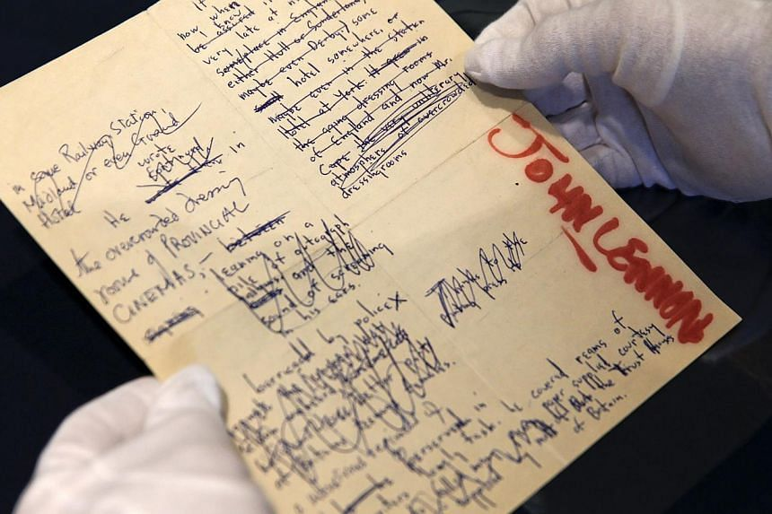 A Sotheby's employee handles a typescript signed by John Lennon during the press preview of a collection of Lennon's original drawings and manuscripts from 1964-65 at Sotheby's in New York on May 29, 2014. -- PHOTO: REUTERS