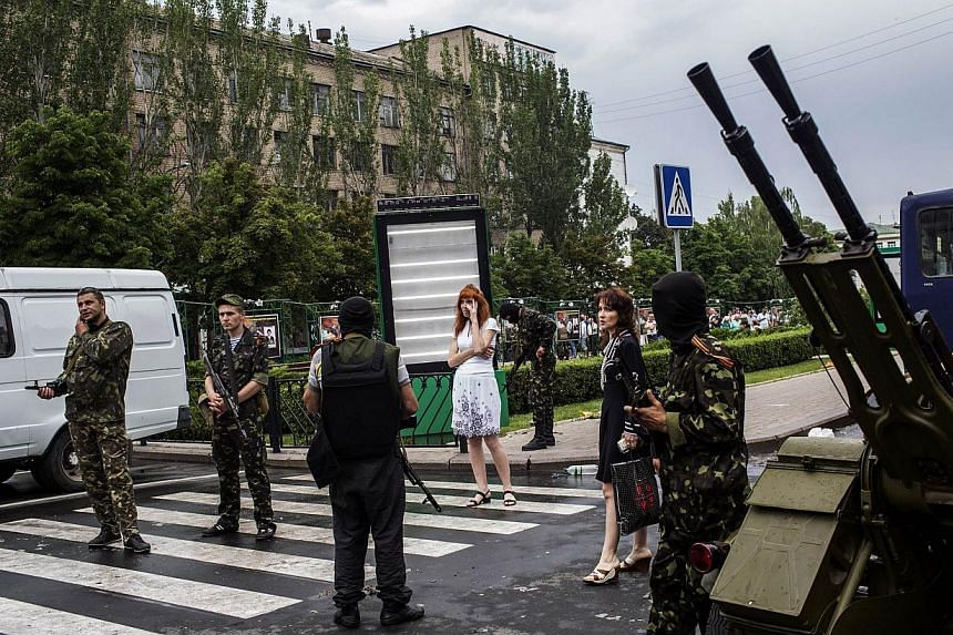 Pro-Russian fighters stand in a street, outside the Donbas building in central Donetsk, on May 29, 2014. Pro-Russian rebels downed a Ukrainian helicopter on May 29, killing 12 soldiers including a general and undermining president-elect Petro Poroshe