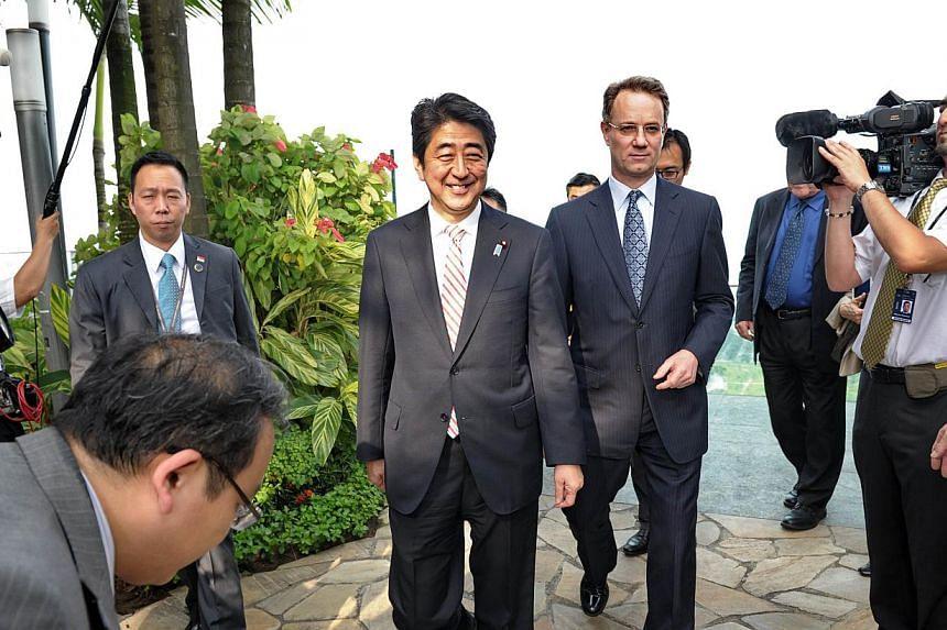 Japanese Prime Minister Shinzo Abe (left) smiles as he walk with George Tanasijevich (right), Marina Bay Sands President and CEO during his visit on the rooftop garden of the Marina Bay Sands on on May 30, 2014 in Singapore.Japanese Prime