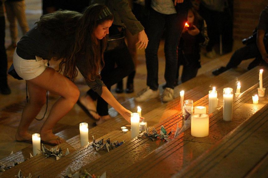 A students places a candle as students of UCSB and UCLA mourn at a candlelight vigil at UCLA for the victims of a killing rampage over the weekend near UCSB on May 26, 2014, in Los Angeles, California. Police officers who visited Elliot Rodger j
