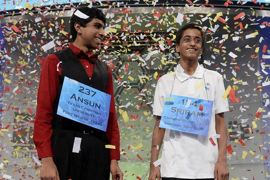 Co-champions of the Scripps National Spelling Bee Ansun Sujoe (left) of Fort Worth, Texas and Sriram Hathwar (right) of Painted Post, New York, stand under falling confetti after winning, at National Harbor, Maryland, USA, on May 29, 2014. -- PHOTO: