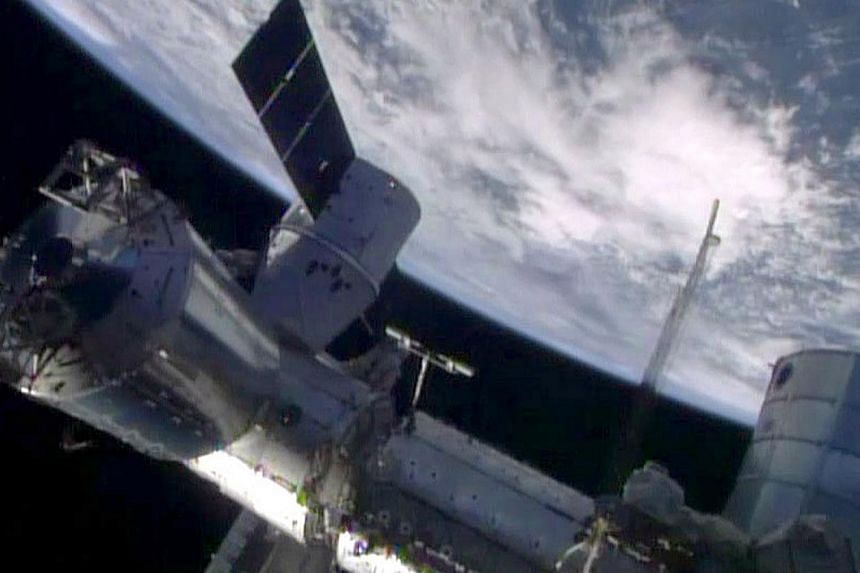 This April 20, 2014 image from Nasa TV shows the SpaceX Dragon cargo craft berthed to the Earth-facing port of the International Space Station's Harmony node. -- PHOTO: AFP