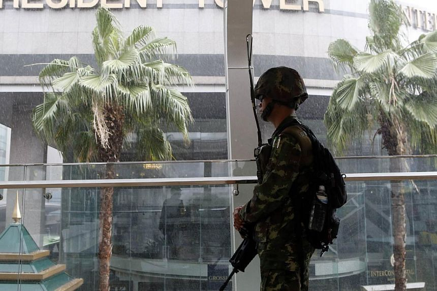A soldier stands guard at an elevated walkway of a shopping district in central Bangkok on May 25, 2014. Thailand is expected to publish data on Friday showing stagnant consumption and investment, more evidence of a stumbling economy that will lend u
