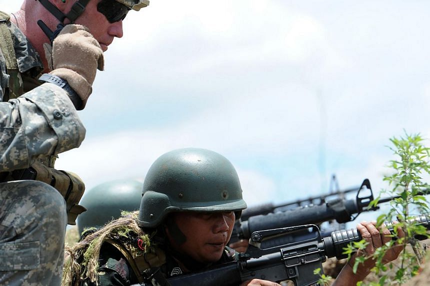 A Philippine soldier (R) fires his weapon while a US soldier (L) supervises during a live fire exercise at a Philippine army training camp in Fort Magsaysay, in Nueva Ecija province north of Manila on May 10, 2014. Philippinelawmaker Carlos Isa