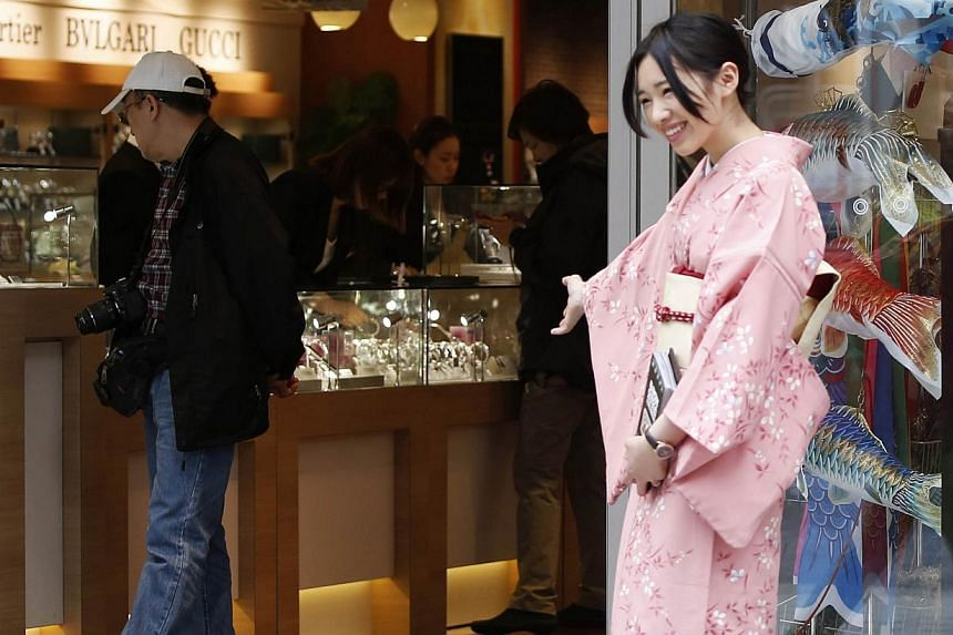 Tourists look at displays at a duty free store as a woman in Kimono welcomes visitors, along a street at Tokyo's Ginza Shopping district on May 15, 2014. Japan is no longer in a deflationary situation with consumer prices and corporate profits rising