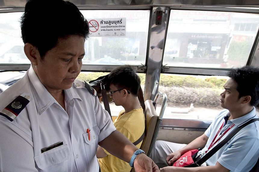 Thai bus fare collector Watcharee Viriya collects fares from passengers as the bus travels on a street in Bangkok. Stuck for hours each day in snarling traffic, bus conductors in Thailand's sprawling capital have found a radical solution to a la