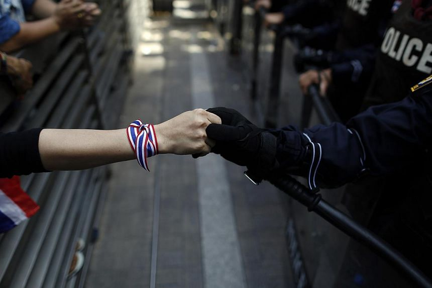 An anti-government protester holds hands with an anti-riot police officer across the closed gates outside the headquarters of the ruling Puea Thai Party of former prime minister Yingluck Shinawatra in Bangkok in this Nov 29, 2013, file photo.Th