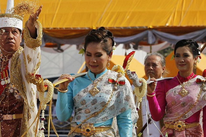 Chavalit Chookajorn (L), permanent secretary of the Thai Ministry of Agriculture and Cooperatives, throws rice grains while dressed in a traditional costume during the annual Royal Ploughing Ceremony, in central Bangkok May 9, 2014. The country's fin
