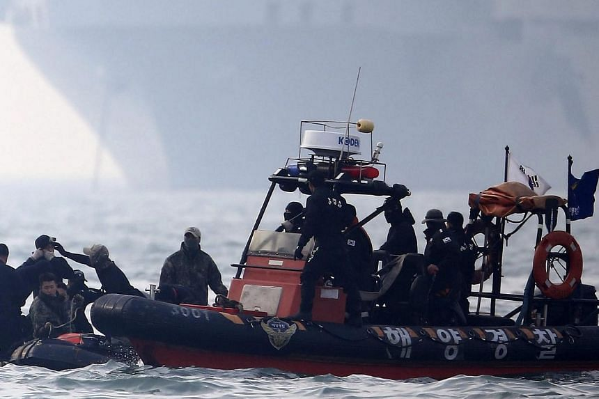 Coast Guard divers prepare to jump into the water during a search and rescue operation for missing people at the ferry Sewol sinking site, at sea, about 20 km off Jindo-port, Jindo Island, in the south-western province of South Jeolla, South Korea, o