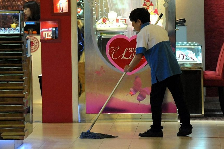 A cleaner mopping the floor in Ang Mo Kio Hub. For the third year in a row, the National Wages Council (NWC) has singled out low-wage workers and recommended they receive a minimum amount of pay increase.-- PHOTO: ST FILE