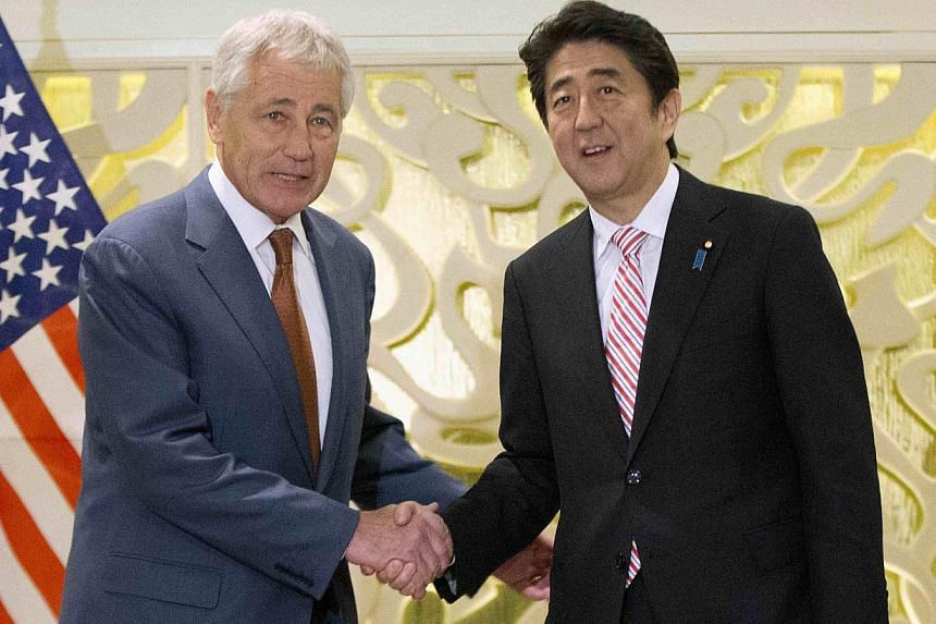 US Defense Secretary Chuck Hagel (left) shakes hands with Japanese Prime Minister Shinzo Abe at the start of their meeting in Singapore, on May 30, 2014. -- PHOTO: REUTERS