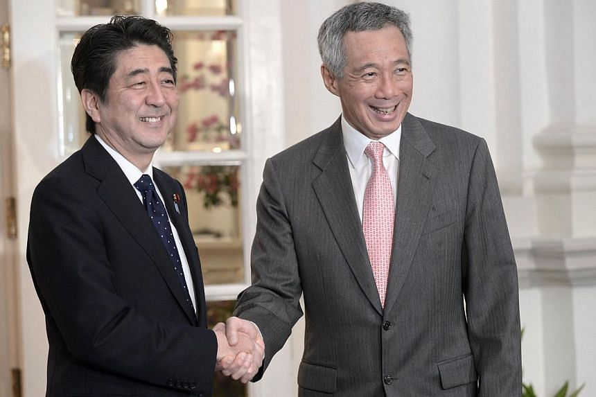 Japanese Prime Minister Shinzo Abe (left) shakes hands with Singapore Prime Minister Lee Hsien Loong (right) during a meeting at Istana Presidential Palace in Singapore, on May 31, 2014. Singapore welcomes Japan's desire to contribute to peace and se