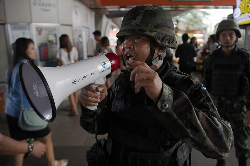 A Thai soldier directs people to a skytrain exit as several ones got closed to Victory Monument, the site of recent anti-coup protests which has been sealed off by security forces to prevent further rallies in Bangkokon May 30, 2014.