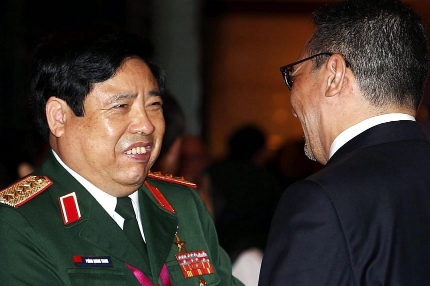 Vietnam's Defence Minister General Phung Quang Thanh (L) greets Malaysia's Defence Minister and acting Transport Minister Hishammuddin Hussein before the 13th International Institute for Strategic Studies (IISS) Asia Security Summit: The Shangri-La D