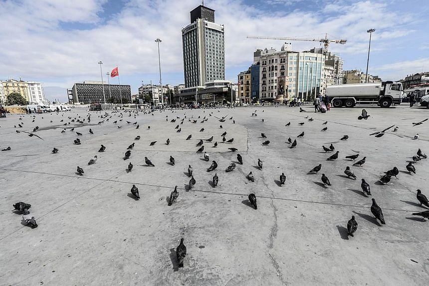 Pigeons roam around an empty Taksim Square on May 31, 2014, after police closed off access to the square during the one year anniversary of the Gezi Park and Taksim Square demonstrations.Turkey's combative primeminister warned protesters