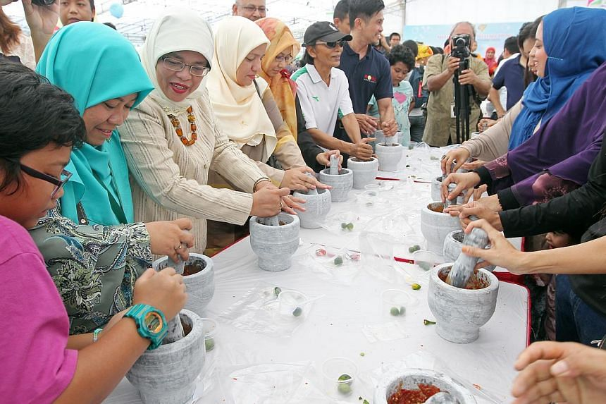 "Speaker of Parliament Halimah Yacob (third from left) at a community carnival to celebrate the 25th anniversary of Muhammadiyah Welfare Home. A hundred people got into the Singapore Book of Records on Saturday for being the ""most number of peopl"