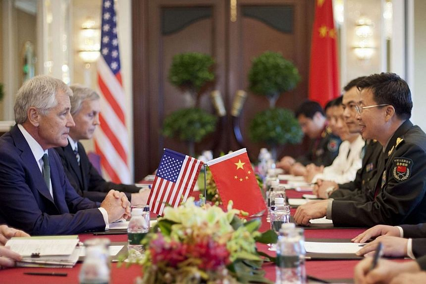 US Defense Secretary Chuck Hagel (left) listens to Lieutenant-General Wang Guanzhong, deputy chief of the general staff of the People's Liberation Army, during the start of their meeting in Singapore on Saturday, May 31, 2014. -- PHOTO: REUTERS