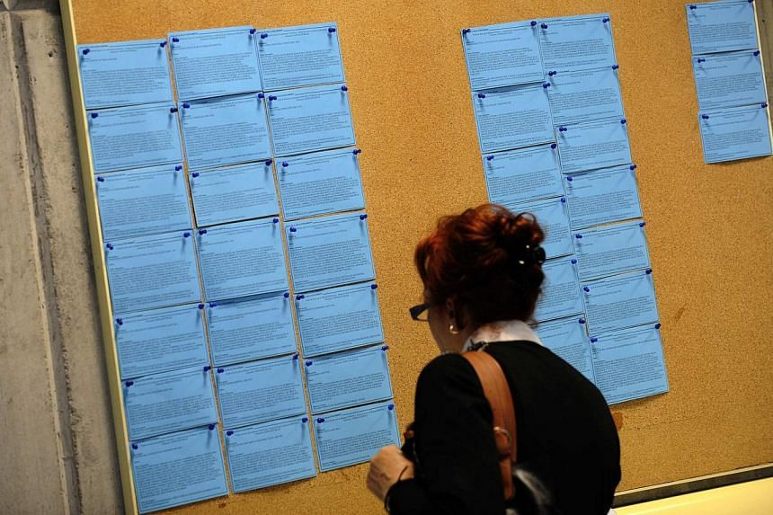 A woman looks at a board with job listings in an unemployment office in Gijon, northern Spain on April 30, 2014. -- PHOTO: REUTERS