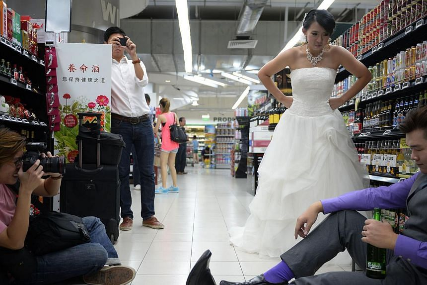 Mr Smith Leong, 30, and his fiancee Chris Goh, 29, pictured during their wedding shoot with photographer Ma Xianrong (left), 30, at the FairPrice outlet in City Square Mall yesterday. -- ST PHOTO: MARK CHEONG