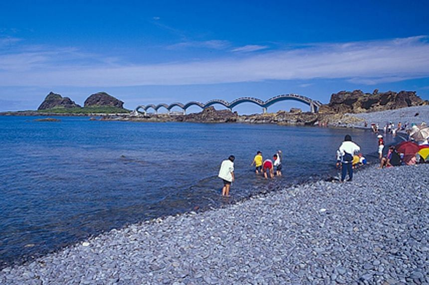 When in Taitung, do not miss Sanxiantai (above), a little islet with three giant boulders facing the Pacific Ocean. At end of an unmarked road in this area, one can soak in views of the sea while watching fishermen in action. -- PHOTO: TAIWAN TOURISM