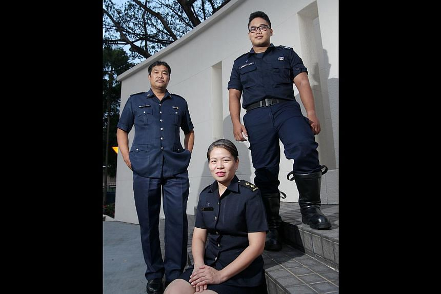 Volunteers who give their time and services include (from left) chauffeur Sha'ari Yakkub (Inspector in the Volunteer Special Constabulary); polytechnic lecturer Lee Bee Lian (Lieutenant in Civil Defence Auxiliary Unit); and student Ahmad Syafi'i (Civ