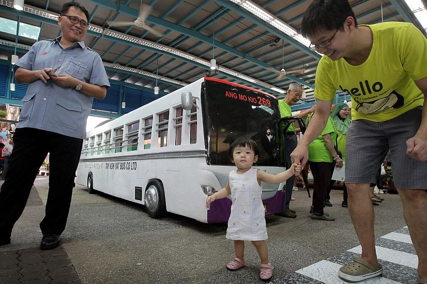 SBS bus captain Mr Fang Chin Poh (left), 53, one-year-old Loo Yan Xuan with her father Mr Jeremy Loo, 35, are seen in front of a 3D SBS bus visual display, which showcases the juxtaposition and contrast that the transport system has undergone since i