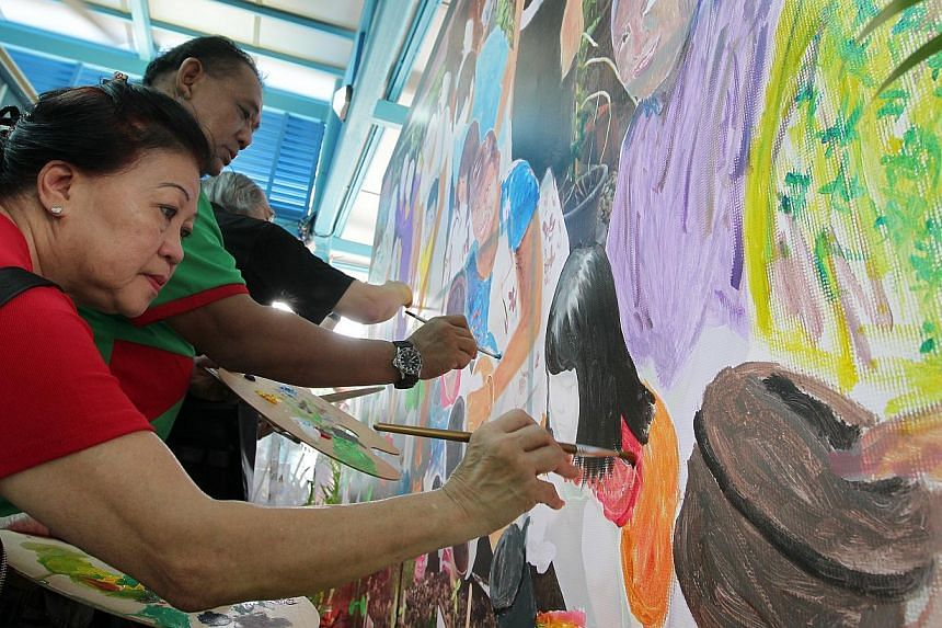 Madam Helene Ong (left), 65, and Mr Muhd Jani Saiyadi, 49, painting on a giant canvas at the arts festival village as part of the PAssionArts Festival 2014, held at the Ang Mo Kio Centre Stage beside Jubilee Square on June 1, 2014. The event runs til
