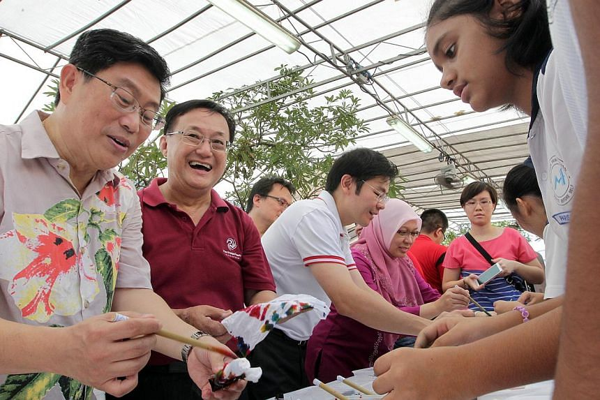 All tied up: (from left) Members of Parliament for Ang Mo Kio GRC Mr Yeo Guat Kwang, Mr Seng Han Thong, together with Minister for Culture, Community and Youth, Mr Lawrence Wong, and MP Dr Intan Azura Mokhtar at a tie-dye booth by Mayflower Primary S